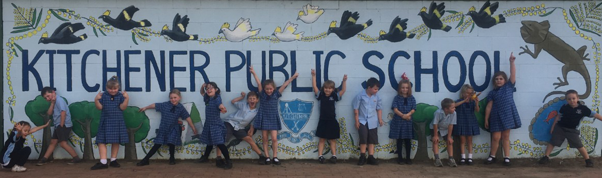 Students in front of our school name mural sign
